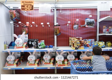 """Manchester, N.H./USA - June 25, 2018: A boy in a shopping cart looks at stuffed animals during the final days of Toys R Us' """"going out of business"""" sale."""