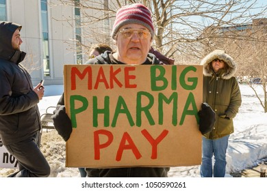 Manchester, NH/USA - March 19, 2018:  Protesters hold signs during the visit of President Donald Trump to a Manchester fire station  to promote his plan to address the opioid epidemic.