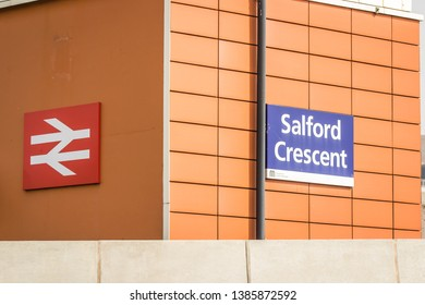Manchester, UK 04/20/2019 Train station of salford crescent presented in signs on the side of the station. The orange brown tan wall is matched well with the red and white and sign.