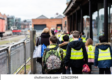 Manchester, Uk - 1st March 2018 - A group of school children walking in the street on a school trip wearing high visibility jackets for safety