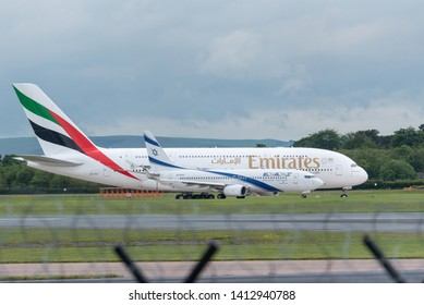 MANCHESTER UK, 30 MAY 2019: Emirates Airbus A380 flight EK18 to Dubai holds on a taxiway prior to takeoff with a much smaller Boeing 737 from El Al Israel Airlines next to it.