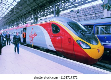 MANCHESTER, UK - APRIL 23, 2013: People exit Virgin Trains Pendolino train in Manchester, UK. Virgin Trains operates since 1997 and as of 2013 uses 56 Class 390 Pendolino train sets.