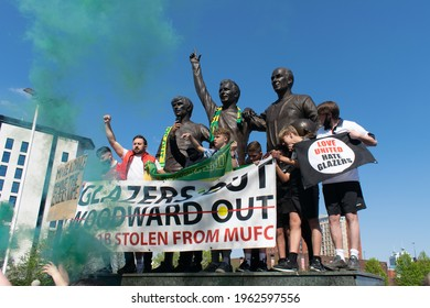 Manchester, UK. April 24, 2021. Protest at Old Trafford football ground with sign Love United Hate Glazers. Trinity statue with green smoke flare at Manchester United Football Club stadium.