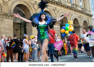 Manchester UK, August 28, 2019. Pride parade passing in front of Radisson Blue Hotel on Peter Street. Hull based drag queen Regina Sparkles followed by man with Prince's Trust t-shirt and heart sign