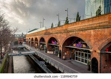 Manchester, UK - February 1 2016: View across the canal at Deansgate Locks with Lola Lo underneath the arches and Beetham Tower/Hilton hotel in the background in Manchester city centre