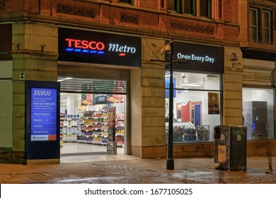 Manchester, UK - February 20 2020: British Tesco Metro supermarket retailer store entrance. External night view of groceries & general merchandise superstore at the city center on 58-66 Market St.