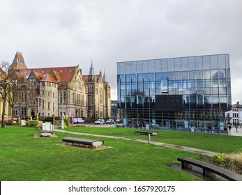 Manchester, UK. February 25, 2020. Manchester University campus, Oxford Road. Gothic revival John Owens building and contemporary Alan Gilbert Learning Commons library with grass covered quadrangle