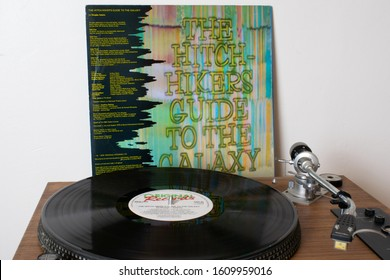 Manchester UK. January 6, 2020. Playing the Hitchhiker's Guide to the Galaxy vinyl album on a direct drive record player. Back cover of Original Records sleeve Don't Panic with album on turntable