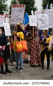 Manchester, UK - July 13, 2018: Trump protest - Female protestors holding signs saying trump go home, not welcome here trump, women empowerment against violence.