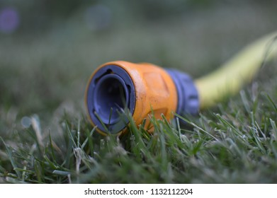MANCHESTER / UK - JULY 2018: Yellow garden hosepipe with water coming out on dry grass. As the hot weather continues water companies across the UK warn that hosepipe bans may be necessary.