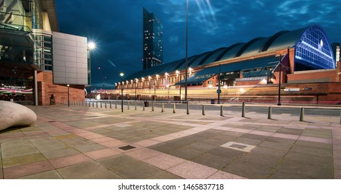 Manchester, UK - July 29, 2019: Long exposure at night of tram passing in Lower Mosley Street with Manchester Central, Beetham Tower and Bridgewater Hall in the back