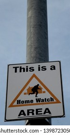 "Manchester / UK - May 15 2019: Closeup of a ""This is a home watch area"" street sign at Chorlton neighborhood in Manchester, UK."