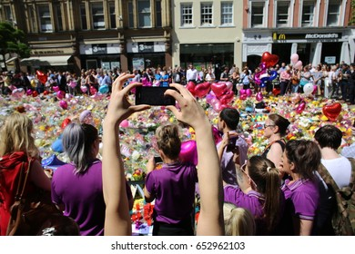 Manchester, UK. May 26th, 2017. A young woman holds a mobile phone up high to photograph the sea of flowers placed in St Ann's Square after the Manchester bombing