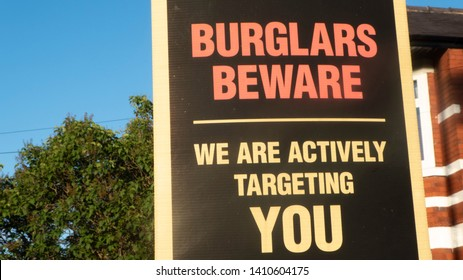 "Manchester / UK - May 28 2019: Close up of a sign by the police stating ""Burglars beware: We are actively targeting you"" in the neighborhood of Chorlton, located in Manchester, UK."