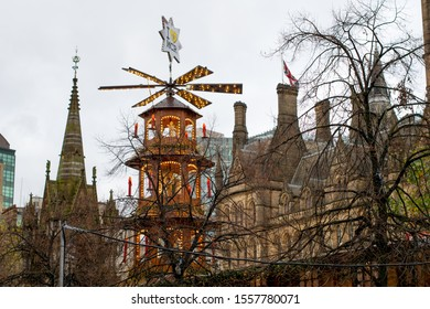 Manchester UK November 12, 2019 Giant Christmas pyramid with lights and star with text I love Manchester and yellow bee in front of Gothic revival architecture of the Town Hall.