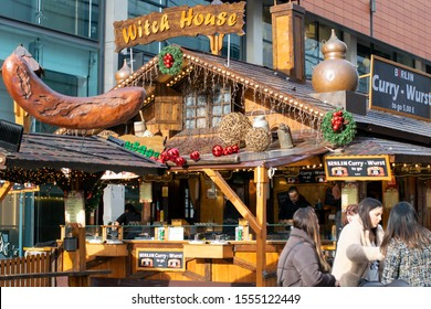 Manchester UK November 8, 2019 Outdoor Christmas markets with Witch House cabin selling curry wurst, preparation of food and group of people sitting