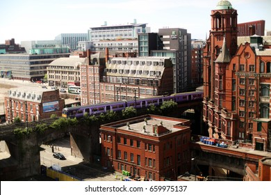 MANCHESTER, UNITED KINGDOM - MAY 27, 2017: A purple train plunges through the northern part of Manchester city making it's way past both older Edwardian buildings and more modern ones