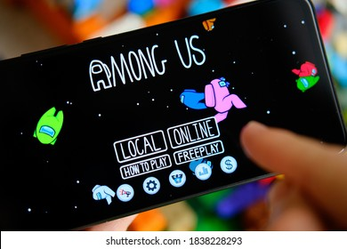 Manchester / United Kingdom - October 21, 2020: Among Us game seen on the smartphone screen and child playing it. New popular app.