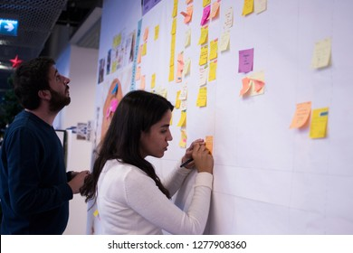 A mand and woman IT workers tracking the tasks on Kanban board. Using Kanban board for task control is a kind of agile development methodology. This picture is taken on 30/12/2018 in Istanbul, Turkey