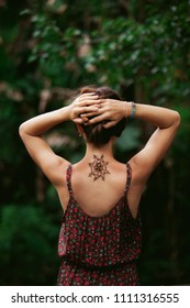 Mandala henna tattoo design on a back side of a neck. Beautiful indian mehendi ornaments painted on a body part