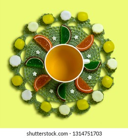 Mandala of tea and sweets on round knitted napkin. Symmetrical pattern of candy and jelly marmalade. Original food concept