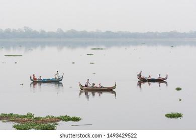 Mandalay, Myanmar - April 2019: tourist having boat ride on Taung Tha Man Lake at dawn