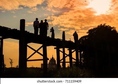 Mandalay, Myanmar - April 29, 2012: People are walking across the Ubein bridge  to see the sunset
