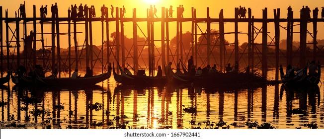 Mandalay, Myanmar (Burma), Sunset with silhouettes of  unrecognizable people U bein Bridge in Amarapura across Ayeyarwady Riverin. U-bein Bridge is oldest and longest teak wooden bridge in the world