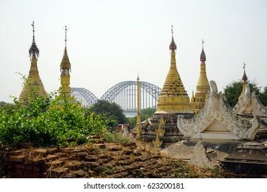 MANDALAY, MYANMAR - CIRCA APRIL 2017  Brick wall, stupas and bridhe