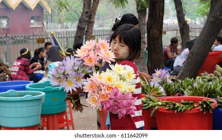 Mandalay, Myanmar - Circa March, 2017 - Unidentified Burmese girl with traditional thanaka on  face selling flowers for worship to tourists at  Temple in Mandalay, Myanmar.