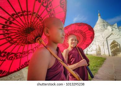 MANDALAY, MYANMAR, -DECEMBER 11, 2017 : Unidentified Two Asian young monk holding red umbrellas on the Mya Thein Tan Pagoda at Mingun, Mandalay Myanmar.
