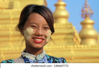 MANDALAY, MYANMAR - DECEMBER 17. 2015: Portrait of a Burmese girl with traditional Thanaka face painting in front of golden Pagoda at Kuthodaw Temple