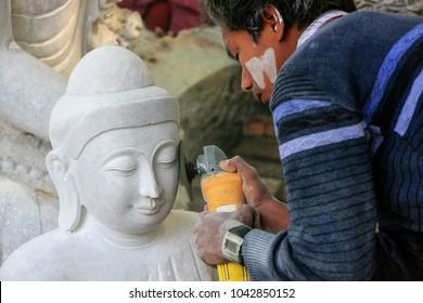 MANDALAY, MYANMAR - DECEMBER 29: Unidentified man works on a statue near Mahamuni Pagoda on December 29, 2011 in Mandalay, Myanmar. Mandalay is the second largest city in Myanmar.