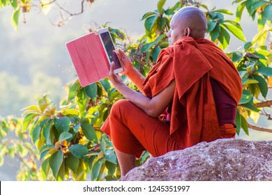 MANDALAY, MYANMAR - DECEMBER 3, 2016: Buddhist monk with his tablet computer on the Mandalay hill, Myanmar