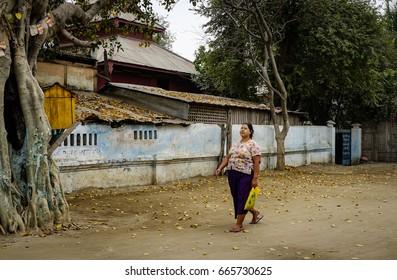 Mandalay, Myanmar - Feb 25, 2016. A woman walking on rural road in Mandalay, Myanmar. Mandalay is the second largest city in Burma, and a former capital of Myanmar.
