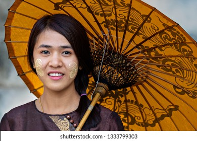 MANDALAY, MYANMAR - FEBRUARY 15, 2019: Local girl with thanaka on her face, in Mandalay, Myanmar. Thanaka is cosmetic paste made from ground bark.