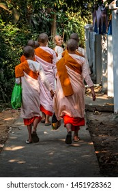 Mandalay / Myanmar - February 20 2018 :  A group of Buddhist nuns returning to the monastery walking away with one nun looking back towards to the camera.