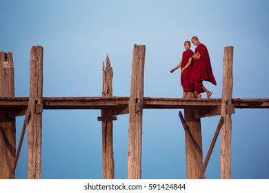 MANDALAY, MYANMAR - JAN 20, 2014: Two buddhist monks talk while walking along U-Bein bridge.
