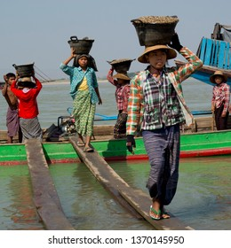 Mandalay, Myanmar - January 28, 2016:  Ballet of Burmese women carrying pebbles in big baskets on their heads. They are walking on a plank between a boat and the shore.