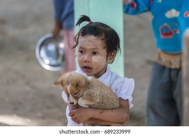 MANDALAY, MYANMAR - JANUARY 5, 2015: Portrait of young cute Burmese girl holding a puppy and wearing thanaka, yellow cosmetic powder paste made from tree bark. Mandalay, Myanmar on January 5, 2015