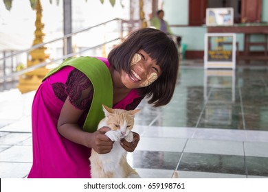 MANDALAY, MYANMAR - JANUARY 6, 2015: Portrait of a young Burmese girl with leaves ornament on her face from thanaka, cosmetic powder paste made from tree bark in Mandalay, Myanmar on January 6, 2015