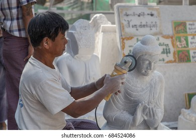 MANDALAY, MYANMAR - JANUARY 6, 2015: Portrait of a man polishing a face of carved stone Buddha statue with grinder in a street workshop in Mandalay, Myanmar on January 6, 2015