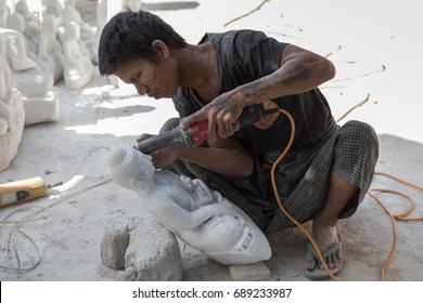 MANDALAY, MYANMAR - JANUARY 6, 2015: Portrait of a man carving a face of stone Buddha statue with grinder in a street workshop in Mandalay, Myanmar on January 6, 2015