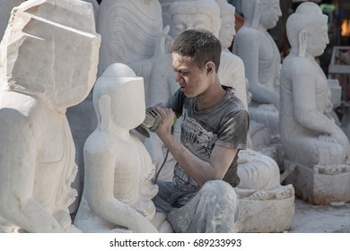 MANDALAY, MYANMAR - JANUARY 6, 2015: Portrait of a man carving Buddha statue from white stone in a street workshop in Mandalay, Myanmar on January 6, 2015