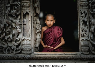 MANDALAY, MYANMAR - JULY 26 2018 : Unidentified young Buddhism novice sitting In front of the door of the temple at Mandalay,Myanma