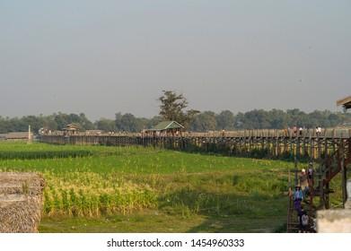 Mandalay, Myanmar- MAR 5: Unidentified Myanmar People in the the farm field by U-Bein bridge in sunset in Mandalay, Myanmar on March 5 2015.
