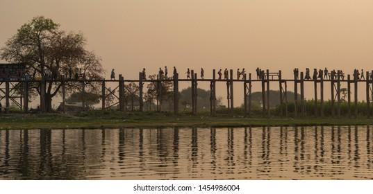 Mandalay, Myanmar- MAR 5: Unidentified Myanmar People on U-Bein bridge in sunset in Mandalay, Myanmar on March 5 2015. The U-Bein bridge is the longest teak bridge in the world, 1.2km length.