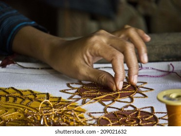Mandalay, Myanmar, March 1, 2014: Burmese woman at work sewing beads. Close up of an artisan hand  that has sew the canvas with beads. Sewing beads onto tapestry has an ancient history in Myanmar