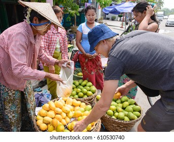 Mandalay, Myanmar - May 17, 2016: Tourist buying ripe mangoes on the street market in Burma. Woman selling fruits to man