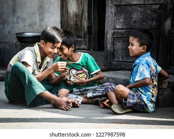 Mandalay, Myanmar - Nov 03 2017: Children playing cards on the street